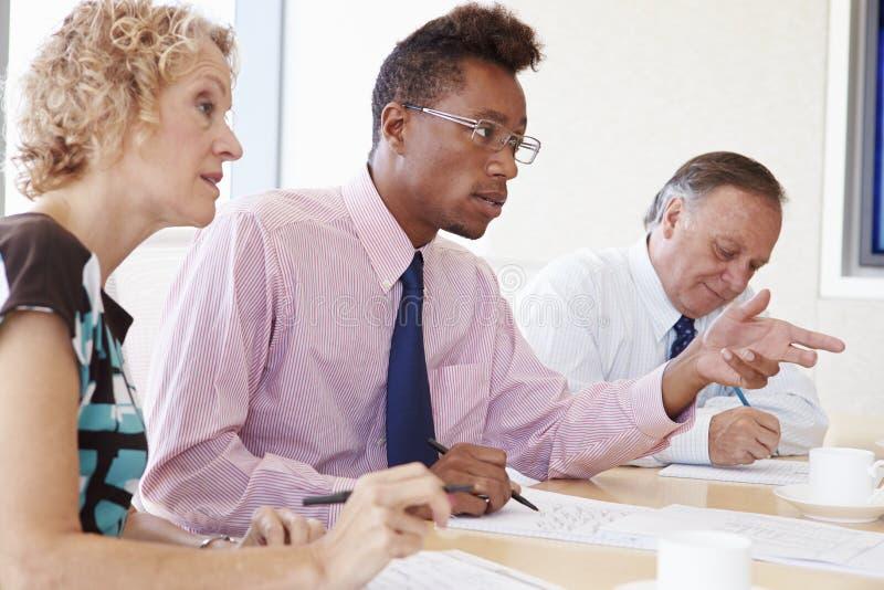 Tre persone di affari che hanno riunione in sala del consiglio fotografie stock libere da diritti