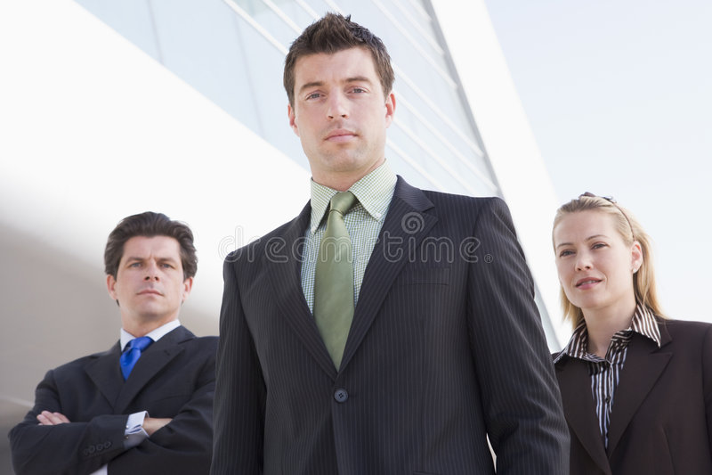 Tre persone di affari che si levano in piedi all'aperto dalla costruzione immagine stock libera da diritti