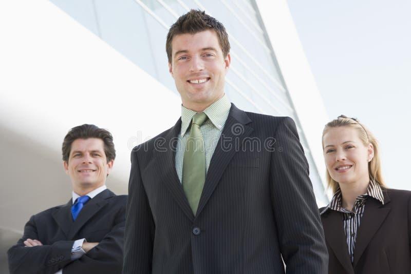 Tre persone di affari che si levano in piedi all'aperto dalla costruzione fotografia stock