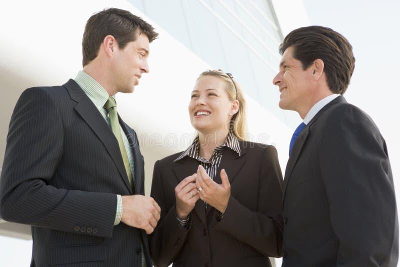 Tre persone di affari che si levano in piedi all'aperto dalla costruzione fotografie stock libere da diritti