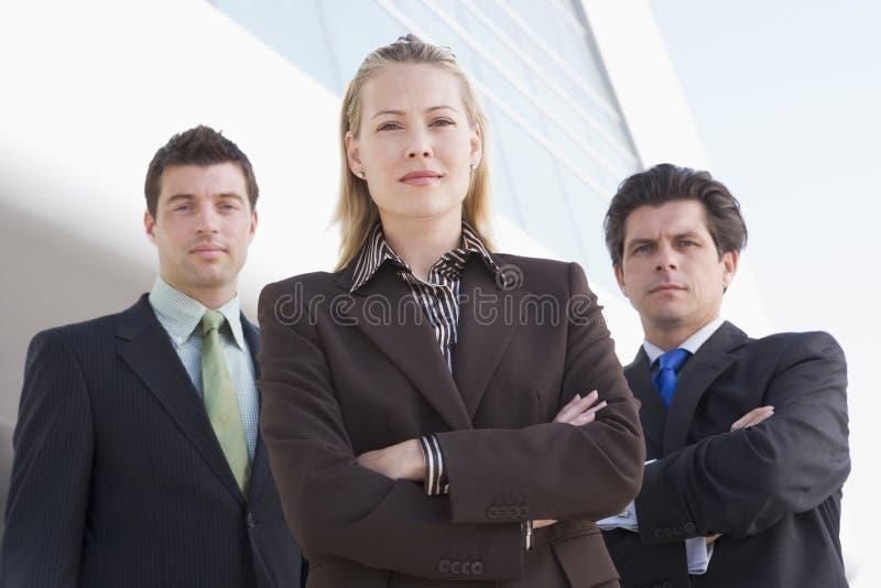 Tre persone di affari che si levano in piedi all'aperto dalla costruzione fotografia stock libera da diritti