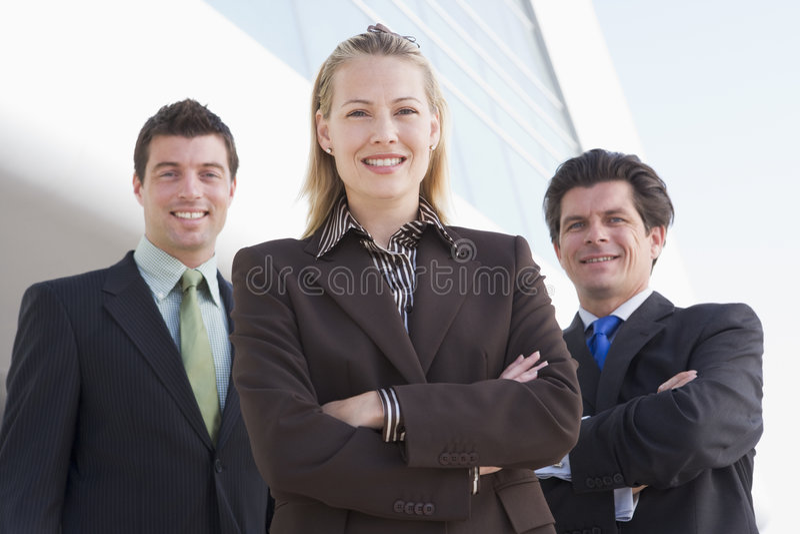 Tre persone di affari che si levano in piedi all'aperto dalla costruzione immagine stock