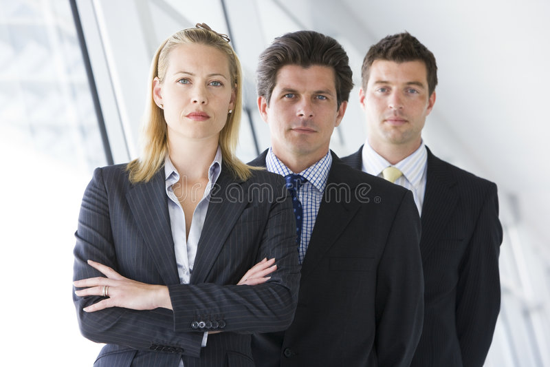 Tre persone di affari che si levano in piedi in corridoio immagini stock