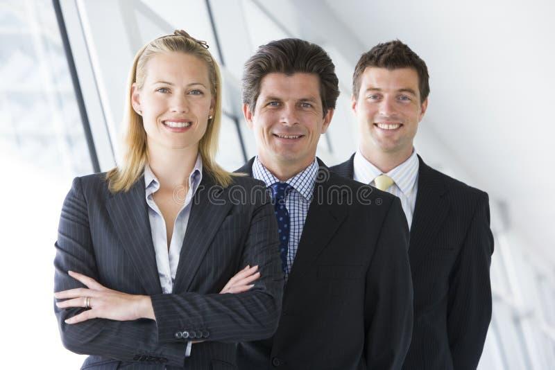 Tre persone di affari che si levano in piedi nel sorridere del corridoio fotografie stock