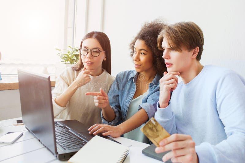 Tre personer förbluffas De ser bärbar dator`-skärmen Grabben rymmer en kreditkort arkivbilder