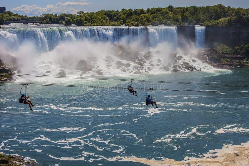 Tre personer går ner bergbanan på bakgrunden av en vattenfall stock illustrationer