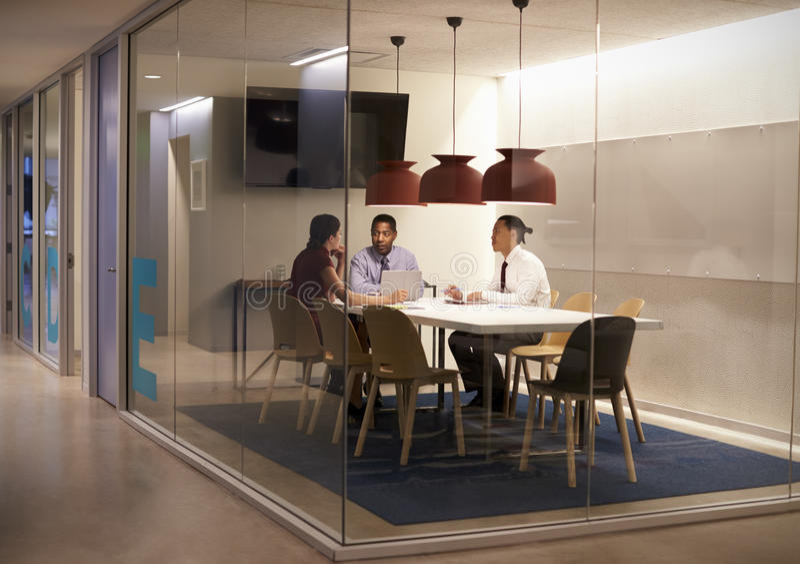 Tre personer i mötesovalkov på en stor företags affär arkivbild
