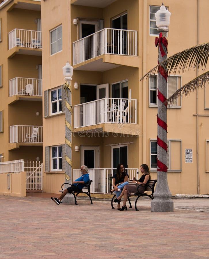 Tre personer på bänkar i Hollywood, Florida royaltyfri bild