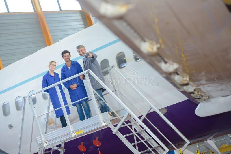 Tre personer på plattformen bredvid flygplan arkivbild