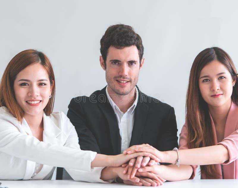 Tre personer räcker tillsammans i begrepp för lag för affärsmöte arkivbilder