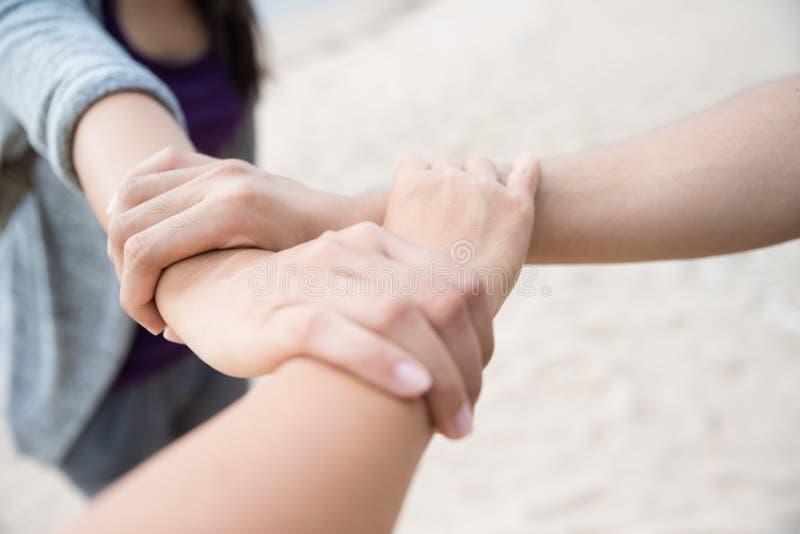 Tre personer sammanfogar händer tillsammans på vit sandstrandbakgrund royaltyfri bild