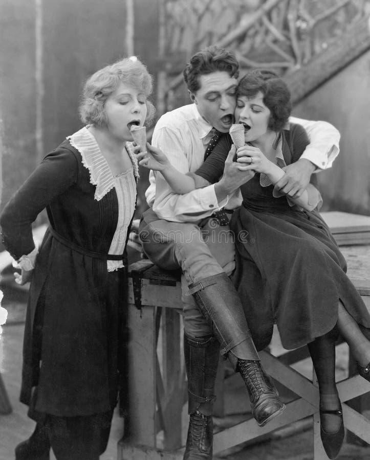 Tre personer som matar sig glasskottar (alla visade personer inte är längre uppehälle, och inget gods finns Leverantörwarran royaltyfri bild