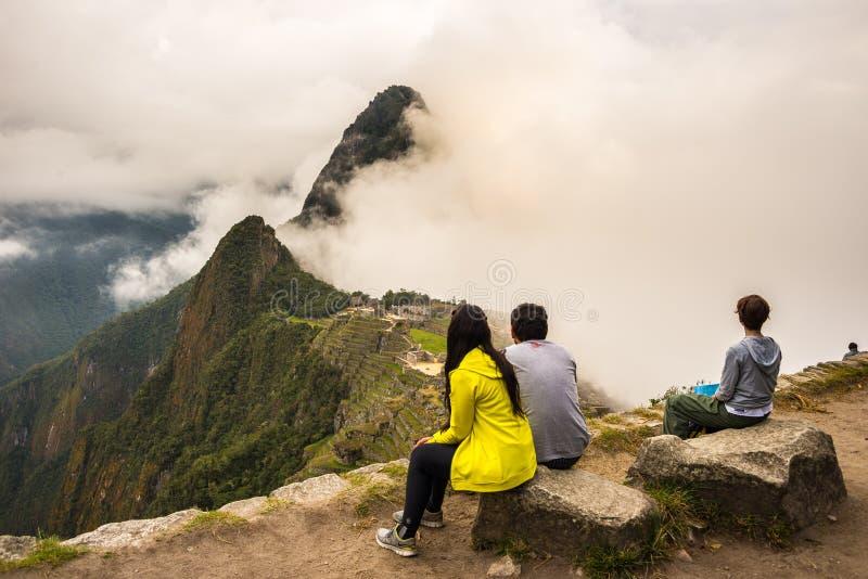 Tre personer som sitter i begrundande av Machu Picchu från terrassen över på dag T arkivbilder