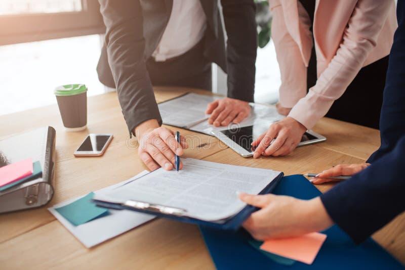 Tre personer som tillsammans arbetar på en talbe i rum De ser dokumentet på den plast- minnestavlan och punkt på den material royaltyfria bilder