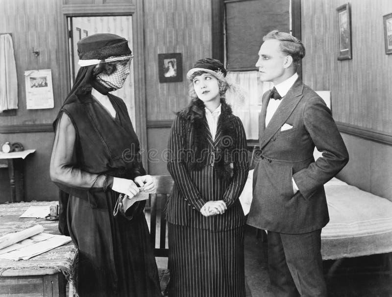Tre personer som tillsammans står i ett rum som talar med de (alla visade personer inte är längre uppehälle, och inget gods finns arkivbild