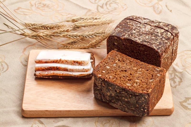 Tre pezzi di bacon salmastro sul pane di segale fotografia stock libera da diritti