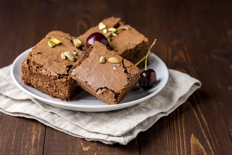 Tre pezzi di brownie casalinghi saporiti del cioccolato sul piatto bianco decorato con la ciliegia ed il fondo di legno dei pista fotografia stock libera da diritti