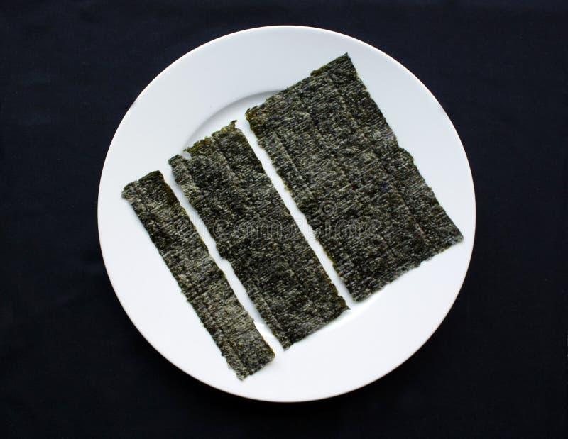 Tre pezzi di nori secco ed urgente disposto su un piatto bianco immagine stock
