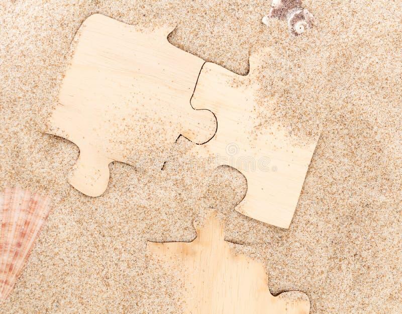Tre pezzi di puzzle di legno in bianco, su fondo sabbioso con le conchiglie immagini stock