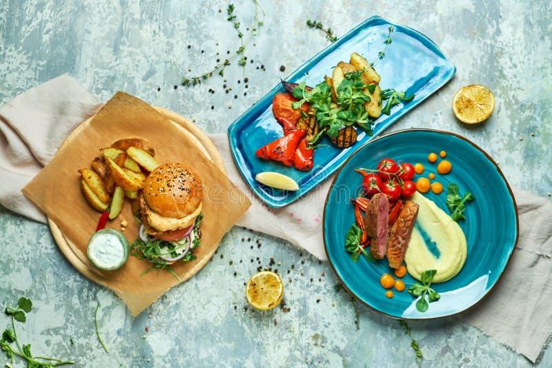 Tre piatti con l'hamburger della carne con le verdure arrostite fotografia stock libera da diritti