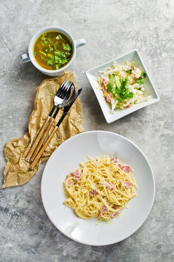 Tre piatti nel ristorante, nella pasta Carbonara, nell'insalata verde e nella minestra di pollo immagine stock