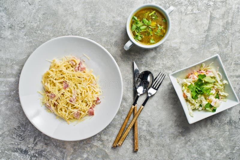 Tre piatti nel ristorante, nella pasta Carbonara, nell'insalata verde e nella minestra di pollo fotografia stock libera da diritti