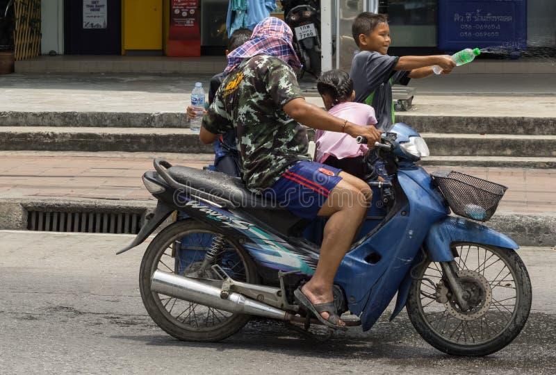 Tre piccoli bambini ed il loro padre su una motocicletta blu stavano giocando i giochi dell'acqua immagine stock