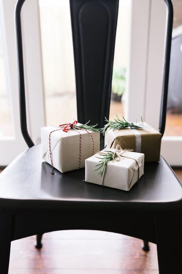 Tre piccoli regali meravigliosamente avvolti su una sedia pranzante fotografie stock libere da diritti