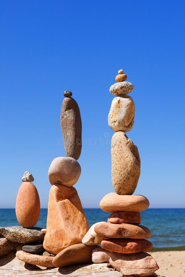 Tre piramidi di zen della roccia dei ciottoli variopinti che stanno sulla spiaggia, sui precedenti del mare Concetto di equilibri fotografie stock