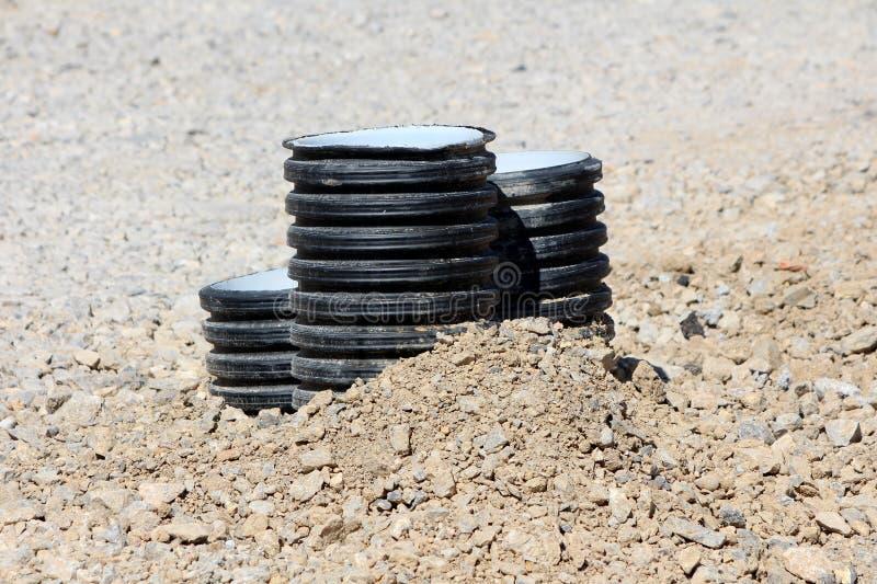 Tre plast- rör som klibbar ut ur jordning som omges med grus på den lokala konstruktionsplatsen arkivfoton