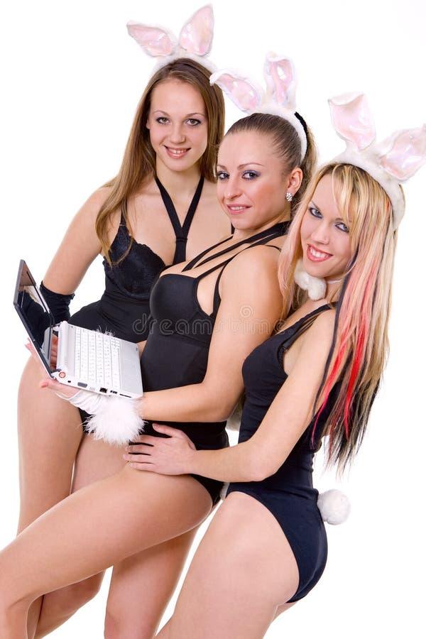 Tre playgirls sexy con le orecchie del coniglietto isolate immagine stock