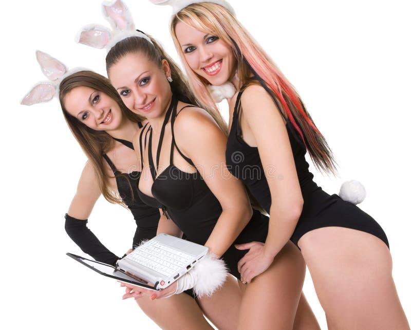 Tre playgirls sexy con le orecchie ed il computer portatile del coniglietto fotografie stock