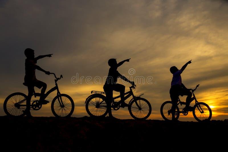 Tre pojkar som cyklar längs framdelen arkivfoto