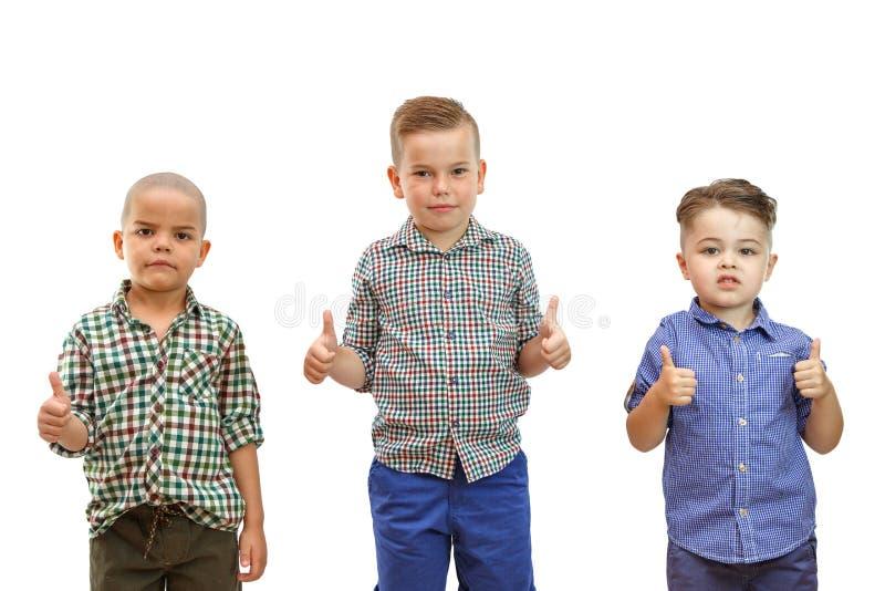 Tre pojkar står tillsammans på den vita bakgrunden och rymmer upp deras tummar royaltyfria foton
