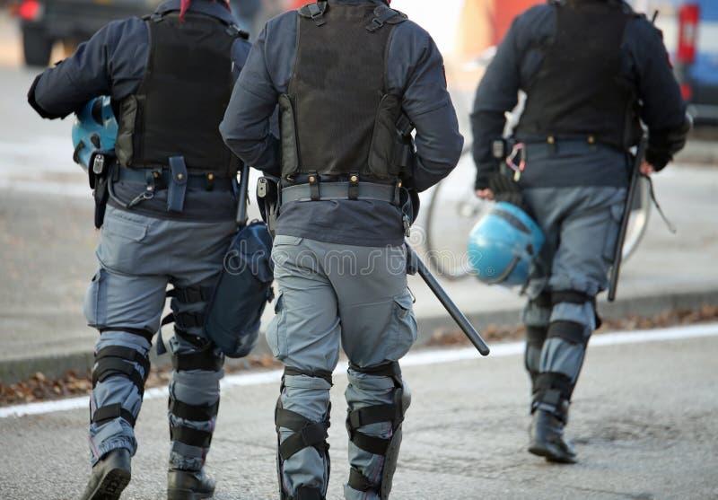 Tre poliser med detskottsäkra omslaget i anti--tumult unifor arkivfoto