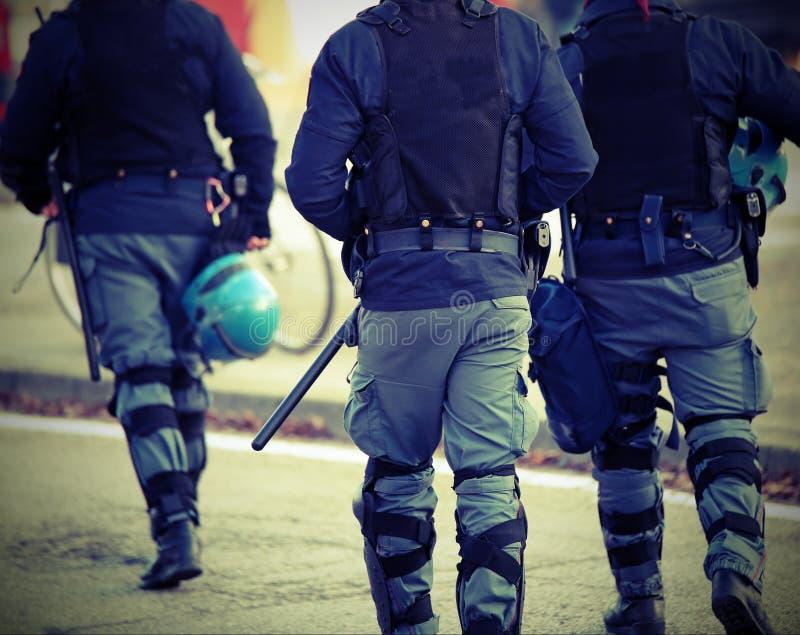 Tre poliser med detskotts?kra omslaget i anti--tumult unifor arkivbild