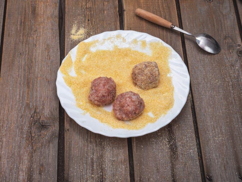Tre polpette del tacchino per la frittura su un piatto con le sabbie di cereale su una tavola di legno della plancia fotografia stock