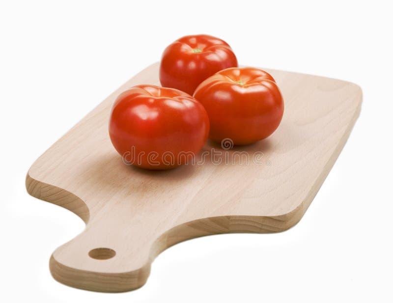 Tre pomodori rossi freschi sulla scheda di taglio immagini stock libere da diritti
