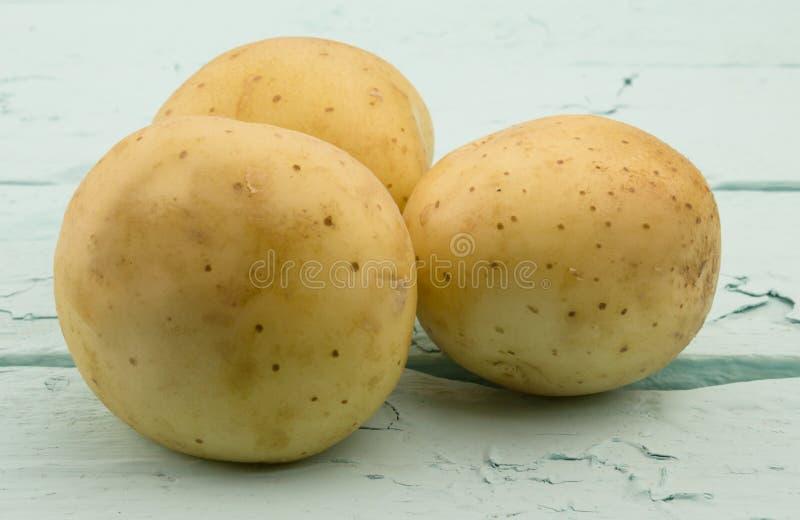 Tre potatisar på trä för havsgräsplan arkivbilder