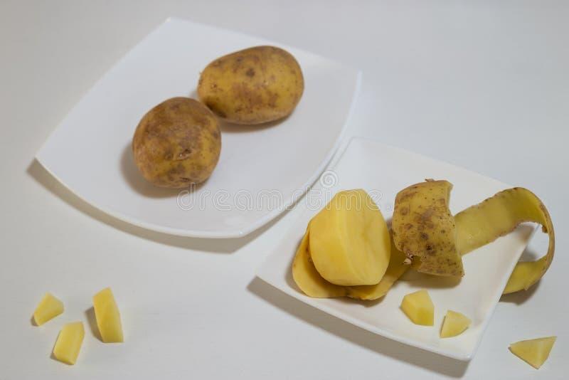 Tre potatisar - som är hela och skalas royaltyfri bild
