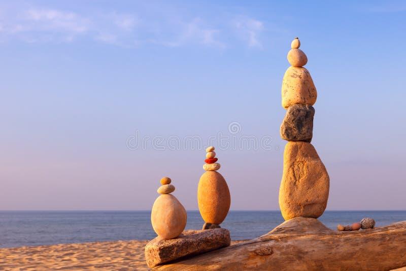 Tre pyramider av färggranulat som står på stranden, frysta, mot havets bakgrund Begreppet balans, harmoni och royaltyfri fotografi