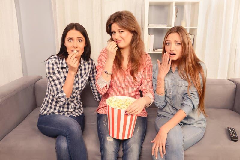 Tre rädda flickor som väntar på film och äter popcorn royaltyfria bilder