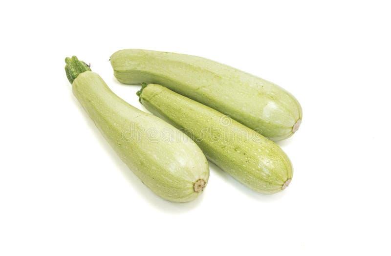 Tre rå zucchinier som isoleras på vit arkivfoton