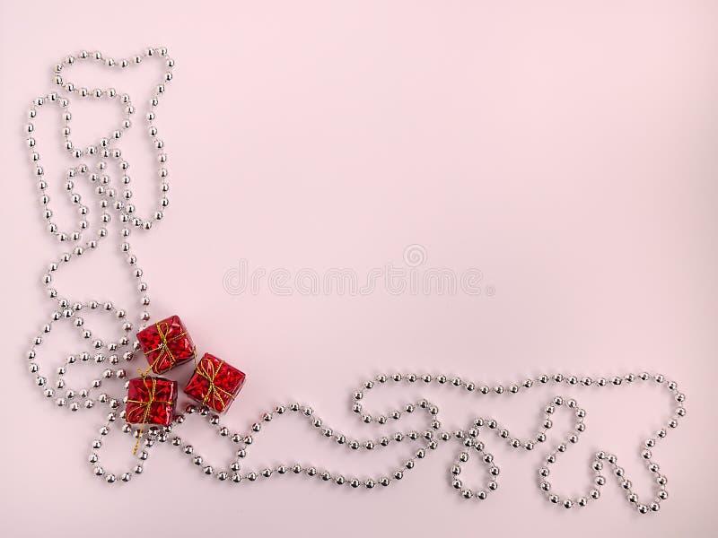 Tre röda askar med gåvor och försilvrar den kulöra pärljulgirlanden på en rosa pastellfärgad bakgrund, den festliga lägenheten lä royaltyfri foto