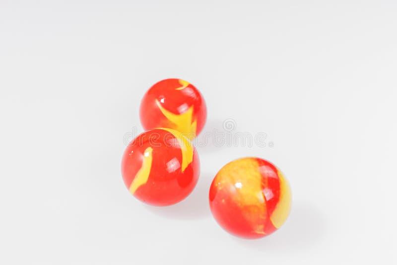 Tre röda gulingmarmor som isoleras på vit fotografering för bildbyråer