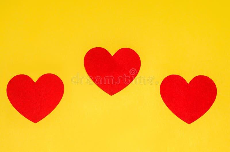 Tre röda hjärtor på en gul bakgrund, begreppet av förälskelse, dagen av dagen för St-valentin` s royaltyfria bilder