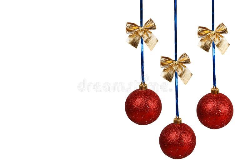 Tre röda julbollar med guld- pilbågar royaltyfri foto
