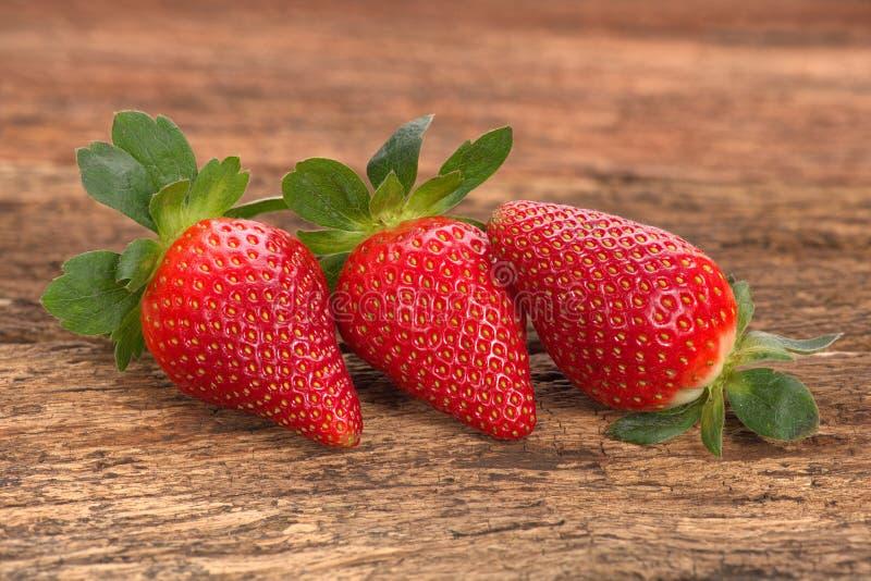 Tre röda mogna jordgubbar som är ordnade på gammal lantlig blicktimmer fotografering för bildbyråer
