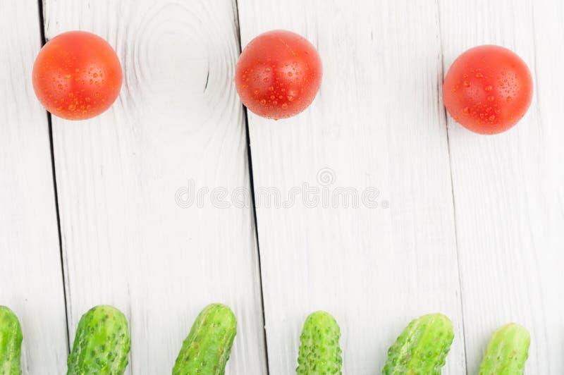 Tre röda mogna tomater och många nya gröna gurkor på träbakgrund arkivbilder