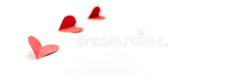 Tre röda pappers- hjärtor som isoleras på vit bakgrund, slut som upp närmast fokuseras på långt baner för hjärta arkivbilder